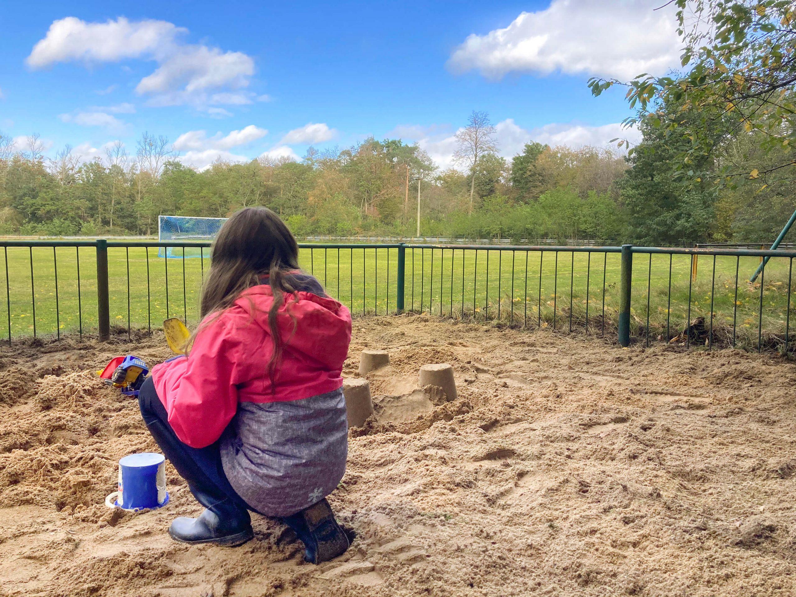Sandkasten mit Person am Sportplatz